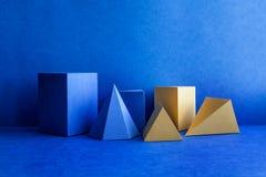 Figuras geométricas ainda composição da vida Cubo retangular do tetraedro amarelo azul tridimensional da pirâmide de prisma imagens de stock royalty free
