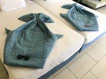 Figuras hermosas de los rayos del mar hechos de las mantas, cubiertas del edredón en la cama con las gafas de sol fotos de archivo