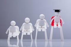 Figuras humanas que sentam-se nas cadeiras brancas e vermelhas foto de stock royalty free
