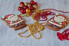 Figuras lindas de Papá Noel hechas de las galletas esmaltadas de la miel que ponen cerca de nudo rojo del arco, de gotas de oro y Fotos de archivo libres de regalías