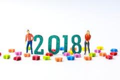 Figuras miniatura del hombre y de la mujer del concepto del Año Nuevo 2018 que colocan o Imágenes de archivo libres de regalías