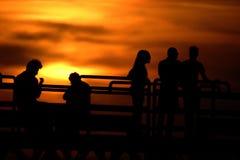 Figuras mostradas em silhueta contra um por do sol de ardência fotografia de stock royalty free