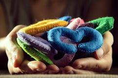 Figuras multicoloras del fieltro en las palmas Imagenes de archivo