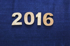 Figuras número de madeira claras 2016 no fundo das calças de brim Fotografia de Stock Royalty Free