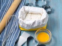 Figuras para cozer o molde de metal cortado, pino do rolo, farinha na tabela de madeira azul, polvilhada com a farinha Copie o es fotos de stock