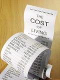 Figuras para el coste de correr las finanzas caseras en un listado de papel Imágenes de archivo libres de regalías