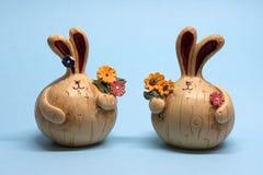 Figuras pequenas de duas lebres com flores em um fundo azul imagens de stock royalty free