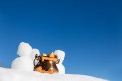 Figuras pequenas dos bonecos de neve e uma bacia com os amendoins na neve Fotos de Stock