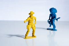 Figuras pl?sticas del juguete del indio azul y del vaquero amarillo fotografía de archivo