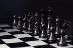 Figuras pretas da xadrez a bordo Grupo de xadrez preto para que o começo do jogo fotos de stock royalty free