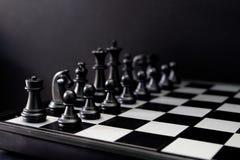 Figuras pretas da xadrez a bordo Grupo de xadrez preto para que o começo do jogo fotografia de stock