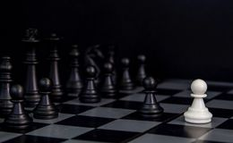 Figuras pretas da xadrez a bordo A xadrez preta figura a fileira na placa quadriculado fotografia de stock royalty free