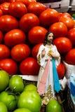 Figuras religiosas en el medio de los tomates rojos y verdes en una parada del mercado fotografía de archivo libre de regalías