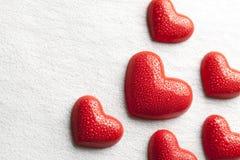 Figuras rojas en la forma de un agua cubierta de rocio del corazón Fotos de archivo
