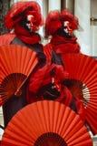 3 figuras venecianas del carnaval en trajes coloridos y máscaras rojos y negros Venecia Italia Imágenes de archivo libres de regalías