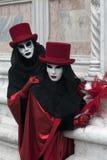 2 figuras venecianas del carnaval en trajes y máscaras coloridos debajo de Venecia Italia Fotos de archivo