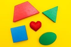 Figuras y corazón en un fondo amarillo fotos de archivo