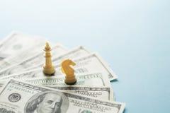 Figuras y dólares americanos del juego de ajedrez en fondo azul con el foco selectivo, planificación de la estrategia empresarial fotos de archivo libres de regalías