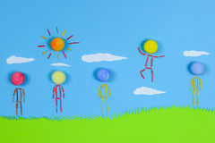 Figurative people standing on grass against blue sky. Stock Photos