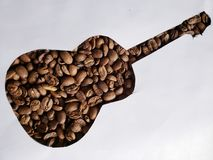 Figure of an acoustic guitar with roasted coffee beans and white background. Backdrop for cafeteria and coffee products, agriculture and harvest, seeds with royalty free stock photography