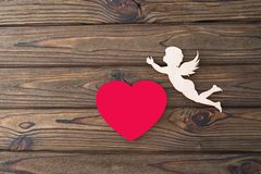 The figure of an angel, the figure of a red heart on a wooden background. Love, the day of valentine`s day Royalty Free Stock Image