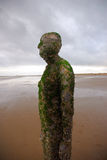 Figure On The Beach. Another Place detail of iron statue on Crosby beach, Merseyside, England Stock Photos