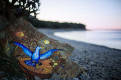 Figure bird on rock which lies the sea. Royalty Free Stock Image