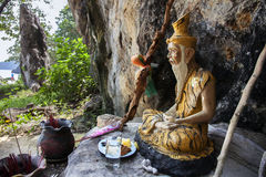 The figure of a Buddhist monk, and offerings on the beach of a t royalty free stock image