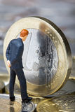 Euro crisis concept. Figure of businessman looking on European Union on one euro coin stock photo