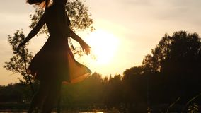 Figure of carefree woman dancing against sunset. Beautiful evening sunlight stock video footage
