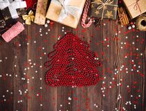Figure of christmas tree made from red beads new year holiday gift box on decorated festive table. With candy cane cinnamon sparkle stars on wooden background Royalty Free Stock Photography