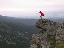 A figure on a cliff. A figure of a woman balancing on the top of a cliff Stock Images