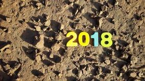 figure colorate per formare il numero 2018 sulla superficie lunare Fotografia Stock