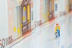 Figure con il carrello e le banconote di acquisto Fotografie Stock