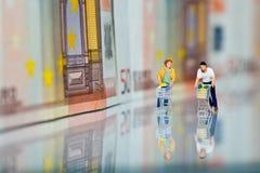 Figure con il carrello e le banconote di acquisto Immagine Stock
