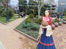 Figure Cossack woman in national dress with loaf in city square, Sochi, Russia. Russian hospitality, sculpture Cossack woman with loaf, walking area with flower Royalty Free Stock Image
