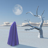 Figure covered by cloth in desert. And dead white tree Royalty Free Stock Photography