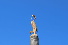 Figure of crane on the stump of a tree against the blue sky. Figures of animals made of wood. Woodcarving.  Stock Image