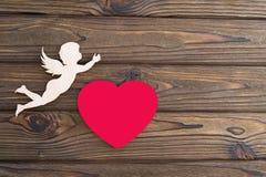 Figure d'un ange, coeur rouge sur un fond en bois Images stock