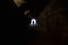 Figure in dark tunnel. Person in dark tunnel, going towards the light. Hope, fear, afterlife concepts Royalty Free Stock Images