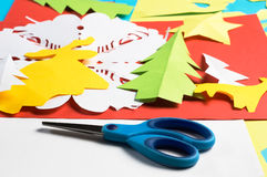 Figure di carta di Natale e di forbici fatte dai bambini, sullo strato di carta rosso Fotografia Stock