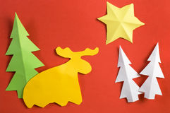 Figure di carta di Natale fatte dai bambini, sullo strato di carta rosso Immagini Stock