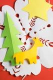 Figure di carta di Natale fatte dai bambini, sullo strato di carta rosso Fotografia Stock