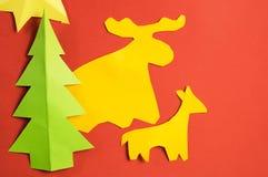 Figure di carta di Natale fatte dai bambini, sullo strato di carta rosso Immagine Stock