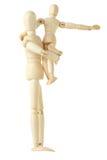 Figure di legno del bambino che si siedono sulle mani del genitore Immagine Stock