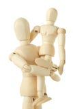 Figure di legno del bambino che si siedono sulle mani del genitore Fotografie Stock