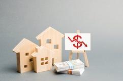 Figure di legno delle case e un manifesto con un simbolo di valore di caduta concetto di diminuzione di valore immobiliare liquid immagini stock libere da diritti