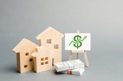 Figure di legno delle case e un manifesto con soldi Il concetto di crescita di valore immobiliare Aumenti la liquidità e l'attra fotografia stock libera da diritti