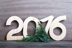 Figure di legno 2016 ed il ramo dell'albero di Natale su gray corteggiano Immagini Stock