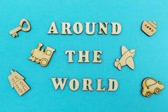 """Figure di legno di un aeroplano, un treno, una nave, un'automobile L'iscrizione """"intorno al mondo """"su un fondo blu immagini stock libere da diritti"""